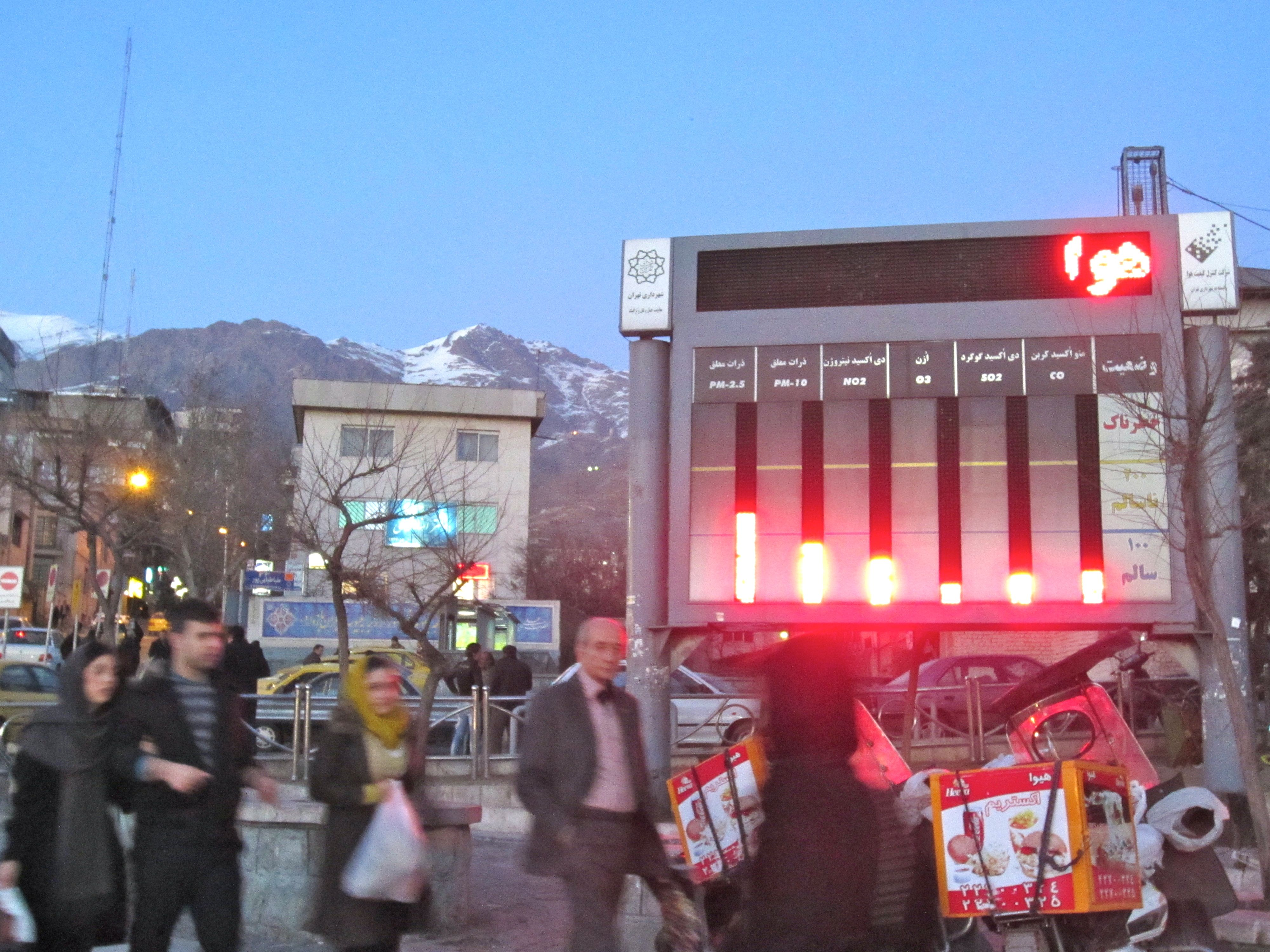 """An electronic display monitors air quality in Tajrish Square, north Tehran. The screen displays levels of various toxins in the air alongside reminders to utilize public transportation. The word at the top is the beginning of a reminder, though so far only the war """"air"""" is visible."""