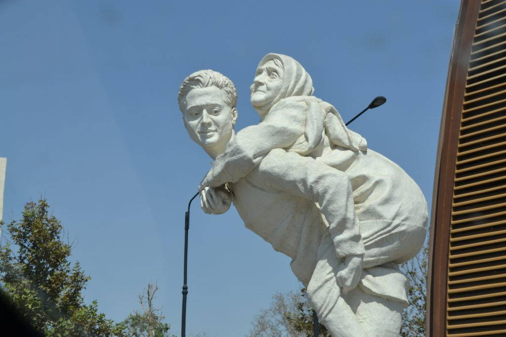 A statue of a son carries his mother on his back