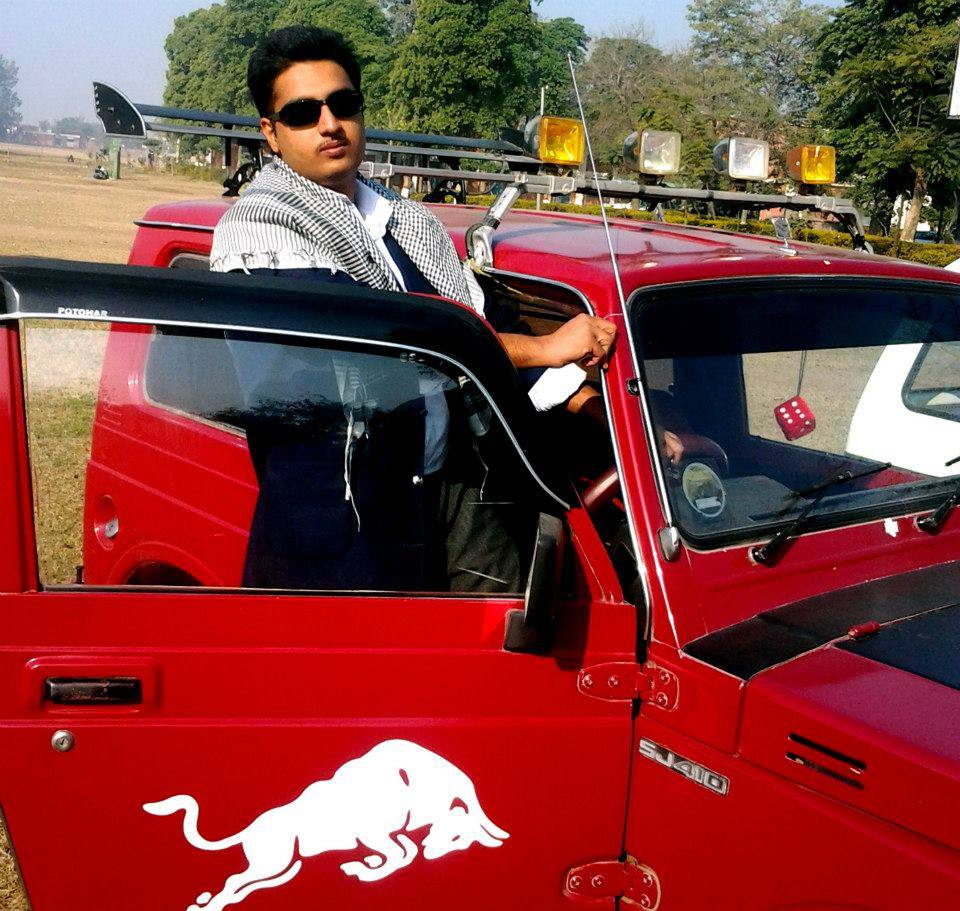 Punjabi rapper Kasim Raja posing with his car