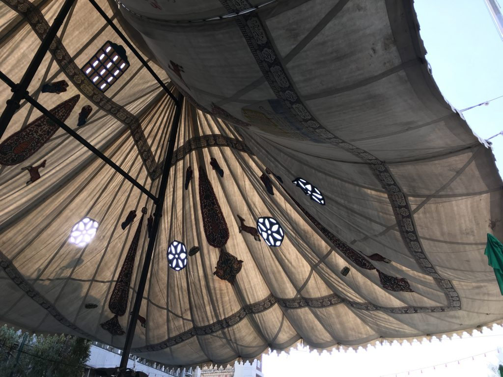 Parts of the street are frequently covered in massive tents representing different neighborhoods. This tent has covered a street leading into Tehran's Grand Bazaar since the Pahlavi period.
