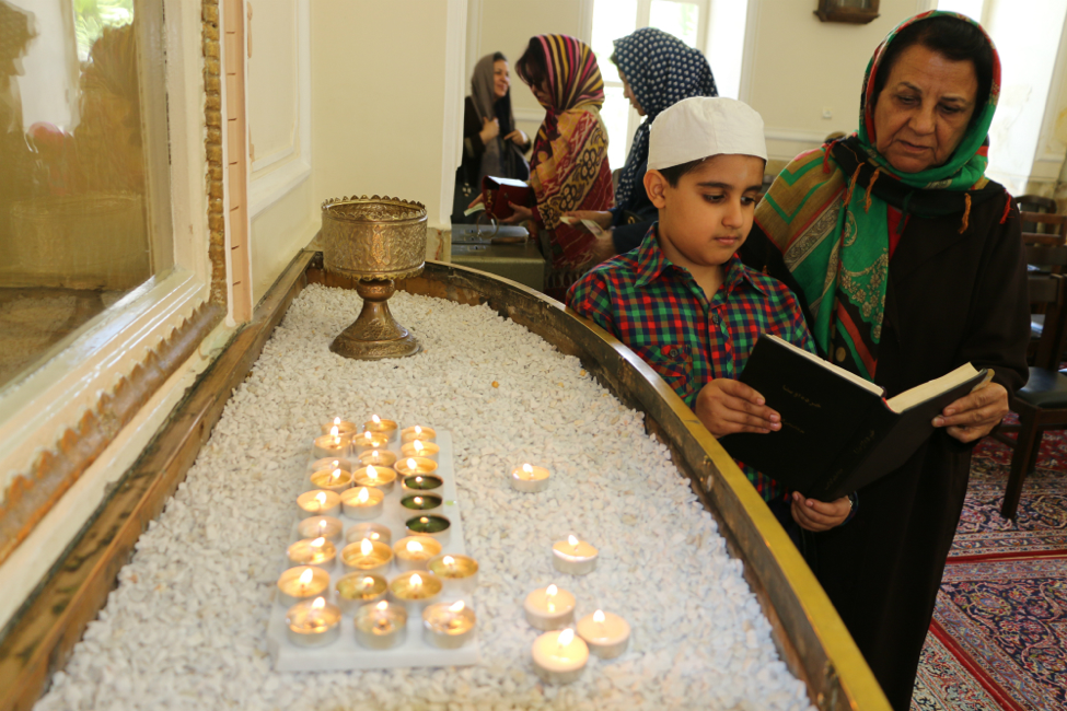 The attendees stand in front of the window of the fire and light the candles on its ledge.