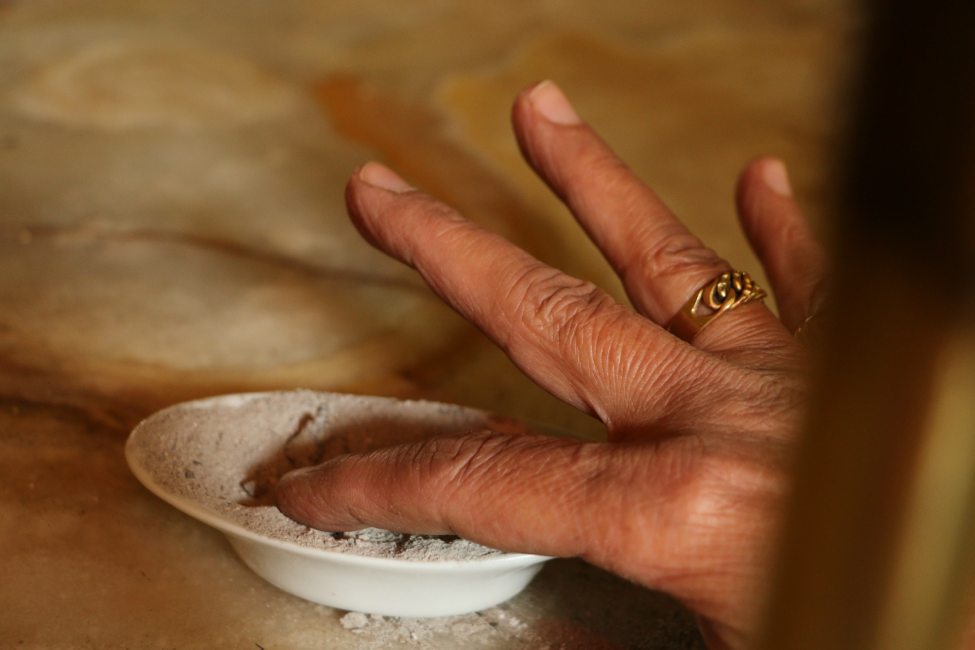 The sacred ash is placed in front of the window of fire. Using their index fingers, attendees spread a little bit of the ash on their foreheads and their necks.