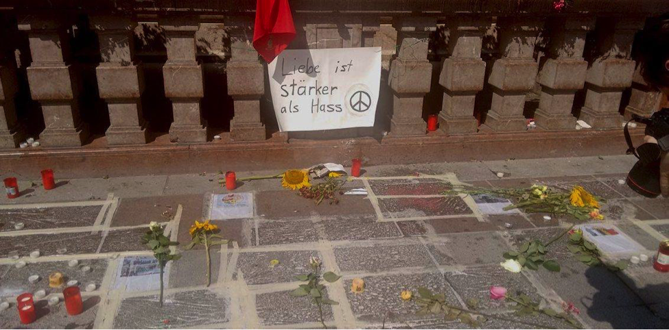 """Part of the memorial for victims of the shooting, in Marienplatz Munich's city center. The handwritten poster reads, """"Love is stronger than hate."""""""
